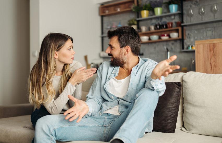 Paar unterhält sich auf der Couch über das Hausbauen